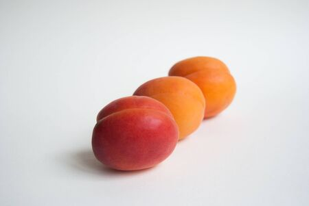 Whole orange and red fresh apricots arranged neatly on the white background