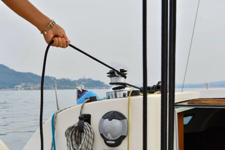 Close-up of the hand with blue nail polish of a female skipper pulling a rope while the sailboat goes