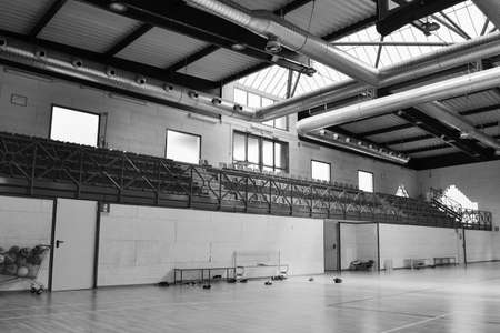 Inside an empty volleyball gym with wooden floor and colorful seats and natural light running through the roof windows