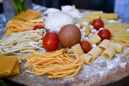 A rustic and raw wooden work table with tagliatelle macaroni dumplings egg flour and tomatoes on it
