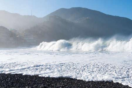 Big wave is breaking on the beach with sunrays filtered from the mountain 스톡 콘텐츠