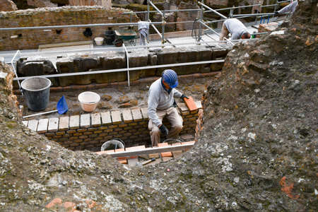 Worker with blue helmet on his head and a brick in his hand as he repairs a Colosseum wall in Italy