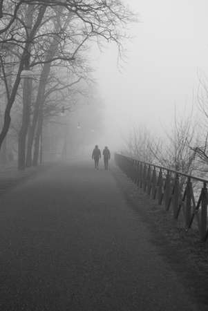 Two women walk in the mist Black and white