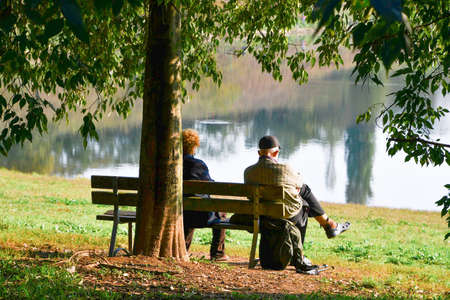 Elderly woman and man sitting admiring the landscape near a small lake with water reflecting the color of the autumn leaves of the trees