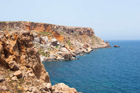 Red and ferrous rocks on the calm and blue sea of Menorca one of the Balearic island in Spain