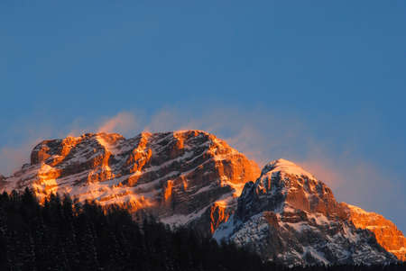 Top of the Dolomites illuminated by the orange light of the sun with snow swept away by the wind - Madonna di Campiglio Italia