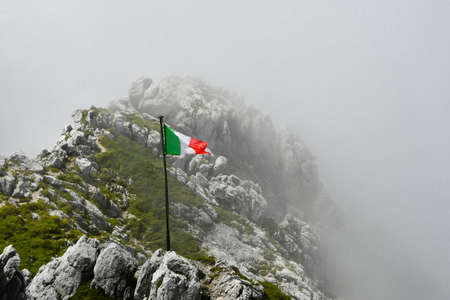 Tricolour flag fluttering over the apex of mountains partially covered by low clouds