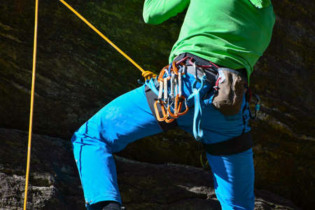Series of carabiners and a chalk-containing bag attached to the harness of a man who is climbing bound and safely