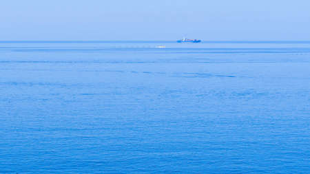 Merchant with blue hull in the open sea with calm sea and cloudless sky with well-defined horizon line