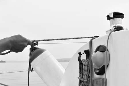 Close-up of a hand pulling a rope while the sailboat goes in black and white 스톡 콘텐츠