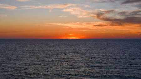 Sun on the horizon with orange sky and some clouds and deep blue ocean