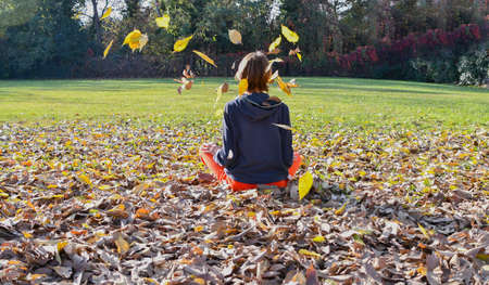 Female in sportswear sitting on a bed of autumn leaves and some falling on her head at the park on a sunny day