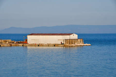 Small freight storage on a pier in the middle of the quiet sea during sunset