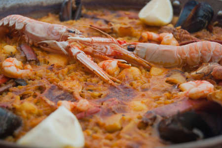 Paella the typical Spanish dish with seafood and prawns and mussels and accompanied by lemon wedges
