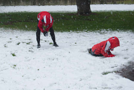 Guys with jacket hoods on their heads fighting snowballs in a park during a snowfall