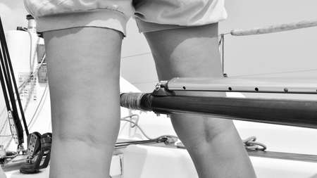 Close-up of a girl skipper's legs as she steers the boat holding the rudder bar between her legs