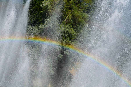 Clearly visible rainbow created among the huge splashes of a fountain