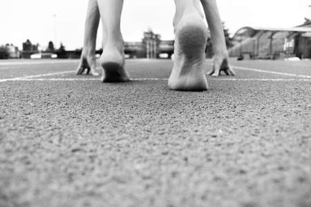 Feet without socks and shoes in the start position on carpet of athletics 스톡 콘텐츠