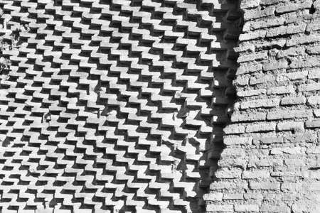 Bricks arranged differently in two walls, one staggered that draw zigzag and oblique lines and the other that draw horizontal lines