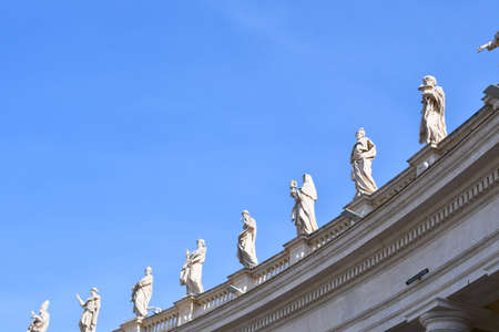 Religious figures in white marble under the columns of Square of San Pietro in Rome during a sunny day with blue sky