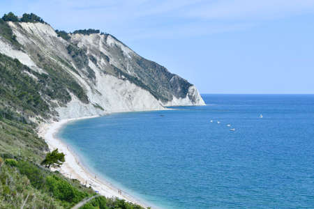 Promontory in the Ancona area in central Italy with long white and empty beach and steep mountain on the sea and marked horizon line