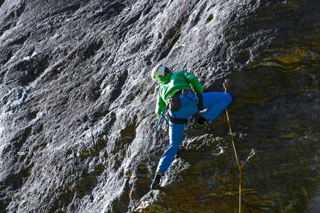 A man climbing tied with a rope to the carabiners on the big wall