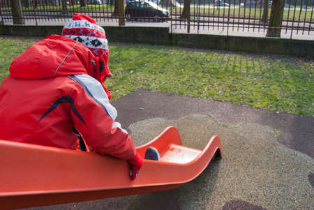 Child in winter jacket, red gloves and hat while sliding on the slide at the playground 스톡 콘텐츠