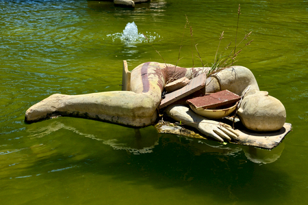 sculpture installation made of stone above the water of a fountain depicting a sleeping human being in fetal position
