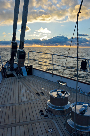 detail of furling equipment on the deck of luxury sailing yacht at the sunset