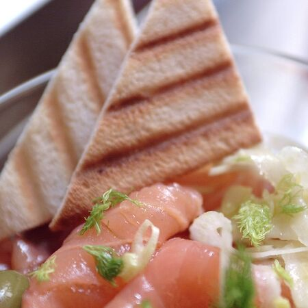 Salmon salad with fennel, toasted bread and capers Foto de archivo