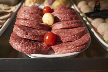 Raw hamburgers on a layer