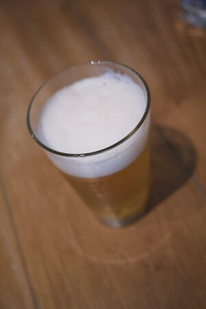A glass of beer on a table Imagens