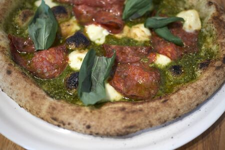 Pizza with salami, pesto and basil