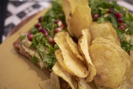 Vegetarian toast with rocket, hummus and pomegranate and chips on the side 写真素材