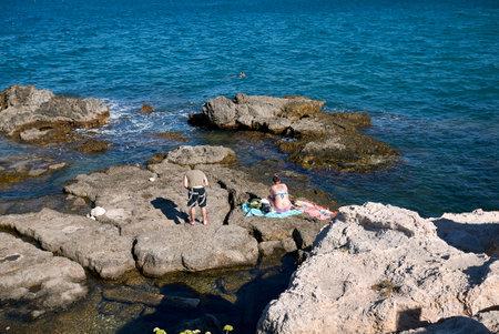 Monopoli, Italy - September 04, 2020: tourist sunbathing on the rocks near Cala di Porta Vecchia beach Editorial