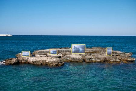 Monopoli, Italy - September 04, 2020: Photographic exhibition in the rocks near Cala di Porta Vecchia beach