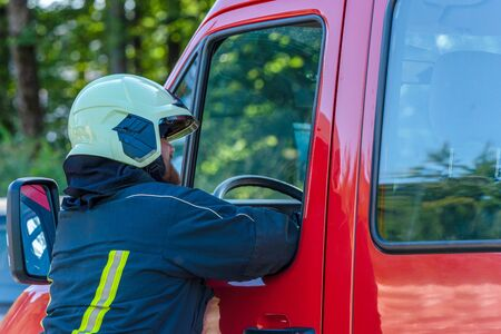 Firefighter in suit and helmet photographed from the side talking to a colleague in a fire truck