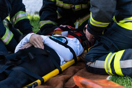The victim in a car accident lies on a stretcher. firefighters help him.