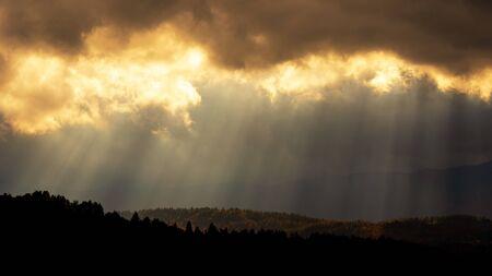 Dunkle Wolken und Sonnenstrahlen. Herbstwaldhügel in schönem goldenem Farblicht