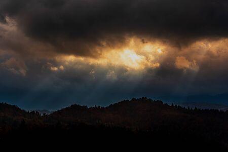 Nuvole scure e raggi del sole. Bosco autunnale punteggiato di raggi dorati.