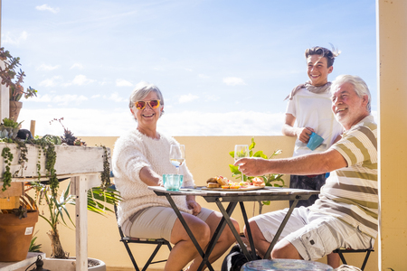 Scene on the rooftop with clear sky in the background. Couple of grandfathers and grandson happy and smile. Plants and summer. Standard-Bild
