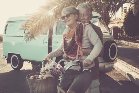 two senior aged couple go bike together in traveler vacation activities. playing and live a funny lifestyle. sun in backlight and old vintage van.