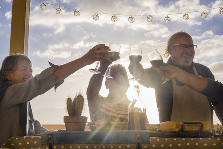 happy group of adults celebrate an event with cups of wine outdoor in the terrace with sunset and backlight. golden tones for happiness lifestyle concept. two men and two women Banque d'images - 102394209