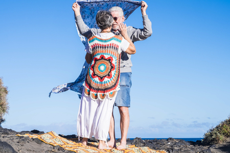 man and woman senior mature people in sweetness and carefree on the ocean coast. vacation or new life retired concept. colorful clothes and scenic place. love and life forever together