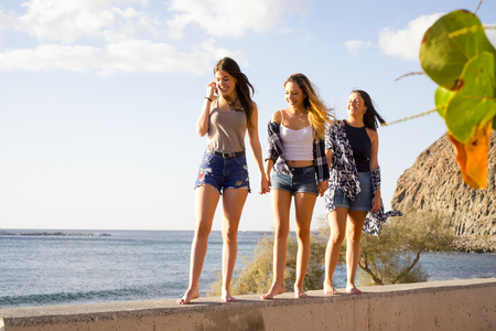 Three young women friends walk together on a wall near the beach in Tenerife. Enjoy the vacation under a blue sky with yellow sun. Hands by hands.