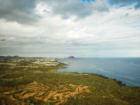 ocean view from countryside in tropical area. cacus and grass plants in arid ground. weather change. beautiful sky with clouds and sea coastline image for touristi pourpuoses