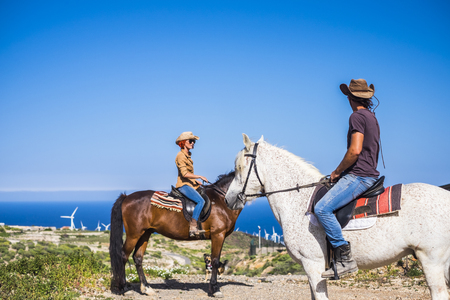 discover nice and amazing places all over the world in alternative way of travel with horses best friends. white caucasian couple in leisure activity outdoor near a windmill farms and under a blue colored sky