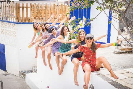 group of seven young smile beautiful woman crazy in vacation and friendship or relationship stay together sit down and go crazy with laugh. summer colors and bright image for joy concept
