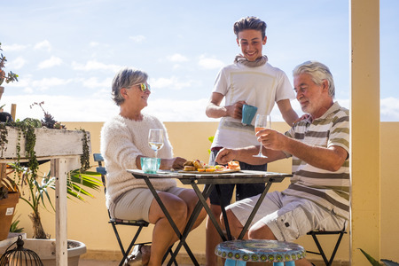 family of different ages with grandparents and grandson spend free time on the terrace eating and drinking on an outdoor terrace in summer Stockfoto