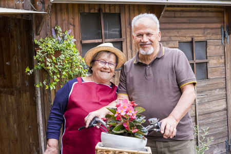 senior couple in love leisure outdoor together on a bike vintage style smiling and having fun under the sun of vacation. alternative way to be retired living on the countryside
